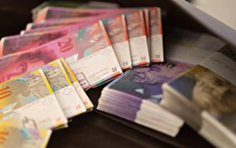 Swiss Franc banknotes sit in the office of a bank in this arranged photograph in Zurich, Switzerland, on Friday, Nov. 20, 2015. The franc is still too strong and the economy not yet back to full health, Swiss National Bank Governing Board member Andrea Maechler said. Photographer: Michele Limina/Bloomberg