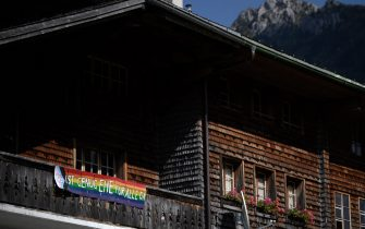 """A picture taken on September 12, 2021 in the Swiss village of Jaun shows a banner hanging from a chalet reading in German: 'It's enough same-sex marriage (EHE) for all"""", ahead of a nationwide votation on the marriage for all. - Swiss citizens are due to vote on September 26, 2021 to determine whether the right to marry should be extended to same-sex couples or not. (Photo by Fabrice COFFRINI / AFP) (Photo by FABRICE COFFRINI/AFP via Getty Images)"""