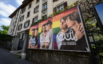 """An electoral poster reading in French: """"Yes I want it"""" ahead of a nationwide votation on the marriage for all is seen, on September 22, 2021 in Lausanne. - While apartment-hunting with his partner 30 years ago, Thierry Delessert was repeatedly asked whether they were cousins, or gay. He knew the latter answer would automatically see their application thrown out. The 56-year-old historian still recalls his run-ins with """"suspicious"""" real estate agents in Switzerland, where police in some places were still keeping registers of homosexuals. Three decades later, in a referendum on September 26, 2021, the wealthy Alpine nation looks set to allow same-sex couples to marry, and grant them the same rights as their heterosexual counterparts. (Photo by Fabrice COFFRINI / AFP) (Photo by FABRICE COFFRINI/AFP via Getty Images)"""