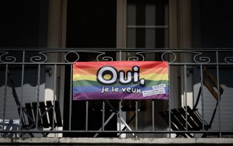"""A rainbow banner reading in French: """"Yes I want it""""  is seen on September 22, 2021 in Lausanne ahead of a nationwide votation on the marriage for all. - While apartment-hunting with his partner 30 years ago, Thierry Delessert was repeatedly asked whether they were cousins, or gay. He knew the latter answer would automatically see their application thrown out. The 56-year-old historian still recalls his run-ins with """"suspicious"""" real estate agents in Switzerland, where police in some places were still keeping registers of homosexuals. Three decades later, in a referendum on September 26, 2021, the wealthy Alpine nation looks set to allow same-sex couples to marry, and grant them the same rights as their heterosexual counterparts. (Photo by Fabrice COFFRINI / AFP) (Photo by FABRICE COFFRINI/AFP via Getty Images)"""