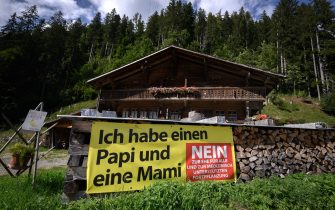 """A picture taken on September 12, 2021 in the Swiss village of Jaun shows an electoral banner against the marriage for all reading in German: """"I have a Daddy and Mummy"""" ahead of a nationwide votation. - While apartment-hunting with his partner 30 years ago, Thierry Delessert was repeatedly asked whether they were cousins, or gay. He knew the latter answer would automatically see their application thrown out. The 56-year-old historian still recalls his run-ins with """"suspicious"""" real estate agents in Switzerland, where police in some places were still keeping registers of homosexuals. Three decades later, in a referendum on September 26, 2021, the wealthy Alpine nation looks set to allow same-sex couples to marry, and grant them the same rights as their heterosexual counterparts. (Photo by Fabrice COFFRINI / AFP) (Photo by FABRICE COFFRINI/AFP via Getty Images)"""