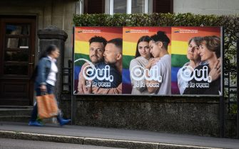 """A woman walks past an electoral poster reading in French: """"Yes I want it"""" ahead of a nationwide votation on the marriage for all, on September 22, 2021 in Lausanne. - While apartment-hunting with his partner 30 years ago, Thierry Delessert was repeatedly asked whether they were cousins, or gay. He knew the latter answer would automatically see their application thrown out. The 56-year-old historian still recalls his run-ins with """"suspicious"""" real estate agents in Switzerland, where police in some places were still keeping registers of homosexuals. Three decades later, in a referendum on September 26, 2021, the wealthy Alpine nation looks set to allow same-sex couples to marry, and grant them the same rights as their heterosexual counterparts. (Photo by Fabrice COFFRINI / AFP) (Photo by FABRICE COFFRINI/AFP via Getty Images)"""