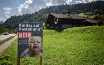 """An electoral poster showing a baby crying and reading in German: """"Children on demand? No to sperm donation and marriage for all"""" is seen ahead of a nationwide votation on the marriage for all in Zweisimmen, Berner Oberland, on September 12, 2021. - While apartment-hunting with his partner 30 years ago, Thierry Delessert was repeatedly asked whether they were cousins, or gay. He knew the latter answer would automatically see their application thrown out. The 56-year-old historian still recalls his run-ins with """"suspicious"""" real estate agents in Switzerland, where police in some places were still keeping registers of homosexuals. Three decades later, in a referendum on September 26, 2021, the wealthy Alpine nation looks set to allow same-sex couples to marry, and grant them the same rights as their heterosexual counterparts. (Photo by Fabrice COFFRINI / AFP) (Photo by FABRICE COFFRINI/AFP via Getty Images)"""