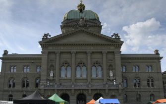 epa08438983 Customers visit the weekly food market in front of the Swiss parliament building, the Bundeshaus in Bern, Switzerland,  23 May  2020. After the Corona-Lockdown food markets in Switzerland have started to reopen under strict restriction for social distancing and hygiene.  EPA/ANTHONY ANEX