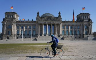 BERLIN, GERMANY - MARCH 25: A woman wearing a protective mask rides a bicycle past the Reichstag where, inside the Bundestag, a massive federal financial aid package is expected to be approved later today to shore Germany up against the effects of the coronavirus (COVID-19) on March 25, 2020 in Berlin, Germany. The Bundestag is expected to pass the package worth over EUR 150 billion later today.  (Photo by Sean Gallup/Getty Images)