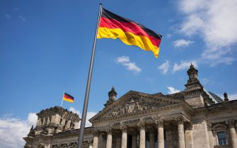 BERLIN, GERMANY - JULY 2014: German flags fly outside the Reichstag, the seat of the German Parliament and one of Berlin's most historic landmarks. It is close to the Brandenburg Gate and before unification was located right next to the Berlin Wall. (Photo by Tom Stoddart/Getty Images) .