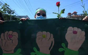 A woman holds a flower during a march demanding the decriminalization of abortion on the Global Day of Action for Legal and Safe Abortion in Latin America and the Caribbean, in San Salvador, on September 28, 2021. -  (Photo by MARVIN RECINOS / AFP) (Photo by MARVIN RECINOS/AFP via Getty Images)