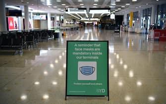 un cartello in aeroporto ricorda di indossare la mascherina