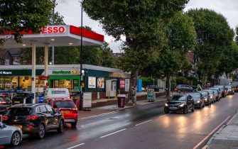 Motorists queue for fuel at an Esso petrol station in London, U.K., on Friday, Oct. 1, 2021. U.K. motorists will have to wait weeks for fuel supply to return to normal, prolonging a shortage that has caused chaos across the country. Photographer: Chris J. Ratcliffe/Bloomberg