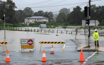 epa09090779 Flash flooding cuts a road at Mudgeeraba on the Gold Coast hinterland, Australia, 23 March 2021. The weather bureau is warning of potentially life-threatening conditions from torrential rain and storms in southern Queensland.  EPA/DAVE HUNT AUSTRALIA AND NEW ZEALAND OUT