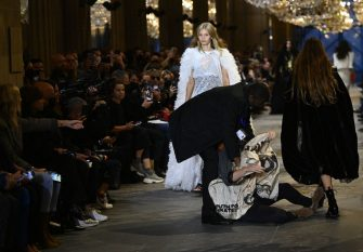 A demonstrator is being evicted by a security member as models present creations by Louis Vuitton during the Women's Spring-Summer 2022 Ready-to-Wear collection fashion show as part of Paris Fashion Week at the Louvre in Paris, on October 5, 2021. - Extinction Rebellion activists burst into the Louis Vuitton fashion show at the Louvre to denounce the impact of the fashion industry on climate change, on the last day of Paris Fashion Week. (Photo by Christophe ARCHAMBAULT / AFP) (Photo by CHRISTOPHE ARCHAMBAULT/AFP via Getty Images)