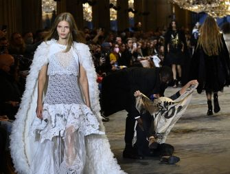 A demonstrator is being evicted by a security member as a model presents a creation by Louis Vuitton during the Women's Spring-Summer 2022 Ready-to-Wear collection fashion show as part of Paris Fashion Week at the Louvre in Paris, on October 5, 2021. - Extinction Rebellion activists burst into the Louis Vuitton fashion show at the Louvre to denounce the impact of the fashion industry on climate change, on the last day of Paris Fashion Week. (Photo by Christophe ARCHAMBAULT / AFP) (Photo by CHRISTOPHE ARCHAMBAULT/AFP via Getty Images)