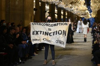 A demonstrator holds a banner as models present creations by Louis Vuitton during the Women's Spring-Summer 2022 Ready-to-Wear collection fashion show as part of Paris Fashion Week at the Louvre in Paris, on October 5, 2021. - Extinction Rebellion activists burst into the Louis Vuitton fashion show at the Louvre to denounce the impact of the fashion industry on climate change, on the last day of Paris Fashion Week. (Photo by Christophe ARCHAMBAULT / AFP) (Photo by CHRISTOPHE ARCHAMBAULT/AFP via Getty Images)