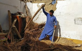 A resident removes debris of his mud house that collapsed following an earthquake in the remote mountainous district of Harnai on October 7, 2021, as around 20 people were killed and more than 200 injured when a shallow earthquake hit southwestern Pakistan in the early hours of October 7. (Photo by Banaras KHAN / AFP) (Photo by BANARAS KHAN/AFP via Getty Images)