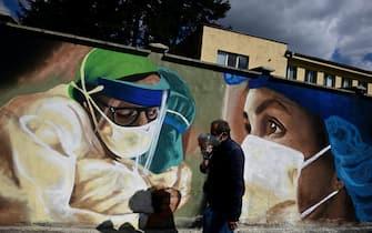 Due persone passano davanti a un murale dedicato a operatori sanitari impegnati nella lotta contro il Covid a Sofia, in Bulgaria