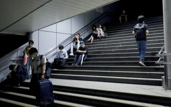 Passengers wait at the Shinagawa station as train services are suspended in Tokyo on early October 8, 2021 after a 6.1-magnitude earthquake shook the Japanese capital and surrounding areas. - - Japan OUT (Photo by STR / JIJI PRESS / AFP) / Japan OUT (Photo by STR/JIJI PRESS/AFP via Getty Images)