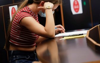 epa09254608 A student (C) reads her test during the University entrance exams at a faculty of Universitat de Barcelona University, in Barcelona, northeastern Spain, 08 June 2021. Some 40,000 students face University entrance exams in Catalonia from 08 June, after a odd school year amid coronavirus pandemic.  EPA/Quique García