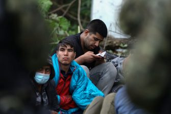 A refugee is seen reading a Koran on 20 August, 2021 in Usnarz Gorny, Poland. Around 32 Afghan citizens are being held in place on the border by Polish border guards and Belarusian forces. The refugees are now pawns in a game between Lukashenko's regime who is expelling them forcefully over the border in retlation for EU sanctions and the Polish government which says it will protect Poland from illegal migrants.In the last weeks Belarusian authorities have been pushing an increasing number of refugees, mainly from Iraq over the borders of Poland, Lithuania and Latvia. (Photo by STR/NurPhoto via Getty Images)
