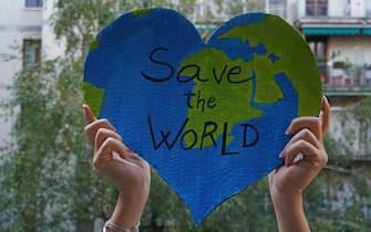 Milano - ragazza ambientalista protesta con cartello Save the wordl, per proteggere la il pianeta dall'inquinamento