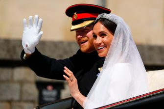 TOPSHOT - Britain's Prince Harry, Duke of Sussex and his wife Meghan, Duchess of Sussex wave from the Ascot Landau Carriage during their carriage procession on Castle Hill outside Windsor Castle in Windsor, on May 19, 2018 after their wedding ceremony. (Photo by PHIL NOBLE / POOL / AFP)        (Photo credit should read PHIL NOBLE/AFP via Getty Images)