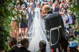 Britain's Prince Harry, Duke of Sussex (R) kisses his wife Meghan, Duchess of Sussex (L) as they leave from the West Door of St George's Chapel, Windsor Castle, in Windsor, on May 19, 2018 after their wedding ceremony. (Photo by Danny Lawson / POOL / AFP)        (Photo credit should read DANNY LAWSON/AFP via Getty Images)