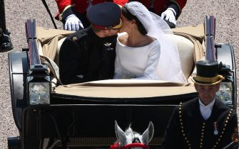 TOPSHOT - Britain's Prince Harry, Duke of Sussex kisses his wife Meghan,  Duchess of Sussex, as they pass through the Cambridge Gate into the grounds of Windsor Castle at the end of their carriage procession in Windsor, on May 19, 2018 after their wedding ceremony. (Photo by Yui Mok / POOL / AFP)        (Photo credit should read YUI MOK/AFP via Getty Images)
