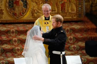 TOPSHOT - Britain's Prince Harry, Duke of Sussex (R) removes the veil of US actress Meghan Markle (L) as they stand at the altar together before Archbishop of Canterbury Justin Welby (C) in St George's Chapel, Windsor Castle, in Windsor, on May 19, 2018 during their wedding ceremony. (Photo by Owen Humphreys / POOL / AFP)        (Photo credit should read OWEN HUMPHREYS/AFP via Getty Images)