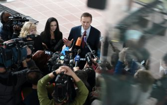 Russian opposition leader Alexei Navalny (C) answers to journalists ahead of a hearing at the European Court of Human Rights (ECHR) in Strasbourg on November 15, 2018. - ?Top Kremlin critic Alexei Navalny heads on November 15 to the European Court of Human Rights which will rule on whether his repeated arrests were politically motivated. The court in Strasbourg must decide whether Navalny, an anti-corruption campaigner and President Vladimir Putin's most vocal critic, was arbitrarily arrested and detained by Russian authorities. Between 2012 and 2014 he was arrested seven times at public gatherings and prosecuted for either breaching procedures for holding public events or disobeying a police order. (Photo by Frederick FLORIN / AFP)        (Photo credit should read FREDERICK FLORIN/AFP via Getty Images)