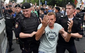 TOPSHOT - Opposition leader Alexei Navalny (C) is detained by Russian police officers during a march to protest against the alleged impunity of law enforcement agencies in central Moscow on June 12, 2019. - More than 50 people including opposition leader Alexei Navalny were detained as police sought to break up a peaceful Moscow rally against the alleged impunity of law enforcement agencies. The unsanctioned rally was initially called to press for the freedom of investigative journalist Ivan Golunov who was last week arrested on trumped-up drugs charges but released on the eve of the march. (Photo by Vasily MAXIMOV / AFP)        (Photo credit should read VASILY MAXIMOV/AFP via Getty Images)