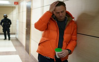 Russian opposition leader Alexei Navalny stands near law enforcement agents in a hallway of a business centre, which houses the office of his Anti-Corruption Foundation (FBK), in Moscow on December 26, 2019. - Russian police on December 26, 2019 conducted fresh searches at Kremlin critic Alexei Navalny's anti-corruption foundation, with his team calling the raid a new bid to disrupt their work. (Photo by Dimitar DILKOFF / AFP) (Photo by DIMITAR DILKOFF/AFP via Getty Images)