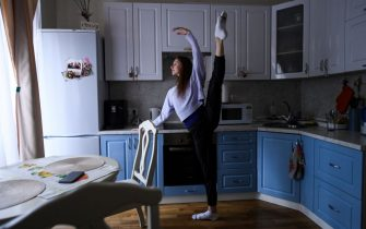 TOPSHOT - Bolshoi theatre first soloist Margarita Shrainer takes part in a training session in the kitchen of her apartment in Moscow on April 29, 2020 during a strict lockdown in Russia to stop the spread of the COVID-19 infection caused by the novel coronavirus. - In the middle of their bedroom, Bolshoi ballet dancers Margarita Shrainer and Igor Tsvirko have placed a linoleum mat and a barre. Since the start of the lockdown, the couple, both soloists in the legendary troupe, have largely used their own initiative to keep up their dance skills at home. (Photo by Kirill KUDRYAVTSEV / AFP) (Photo by KIRILL KUDRYAVTSEV/AFP via Getty Images)