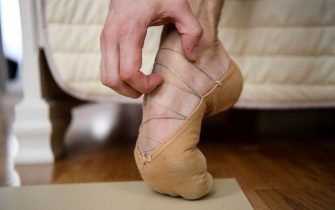 Bolshoi theatre leading soloist Igor Tsvirko scratches his foot as he takes part in a training session in his apartment in Moscow on April 29, 2020 during a strict lockdown in Russia to stop the spread of the COVID-19 infection caused by the novel coronavirus. - In the middle of their bedroom, Bolshoi ballet dancers Margarita Shrainer and Igor Tsvirko have placed a linoleum mat and a barre. Since the start of the lockdown, the couple, both soloists in the legendary troupe, have largely used their own initiative to keep up their dance skills at home. (Photo by Kirill KUDRYAVTSEV / AFP) (Photo by KIRILL KUDRYAVTSEV/AFP via Getty Images)