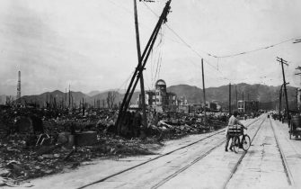 August 1945:  A man wheels his bicycle thorough Hiroshima, days after the city was leveled by an atomic bomb blast, Japan. The view here is looking west-northwest, about 550 feet from where the bomb landed, known as X, on August 6, 1945.  (Photo by Keystone/Getty Images)