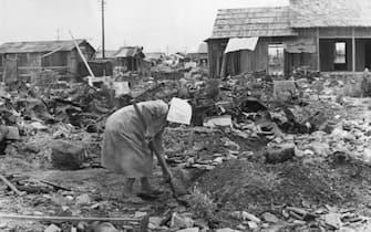 (Original Caption) Hiroshima, Japan: Woman shoveling rubble in ruins of Hiroshima, after Atomic explosion. Photograph, August 1945.