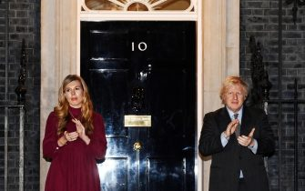 epa08985037 British Prime Minister Boris Johnson (R) with partner Carrie Symonds (L) clap outside 10 Downing Street during a tribute to Sir Captain Tom Moore in London, Britain, 03 February 2021. According to Moore's family, 100-year old Tom Moore, who raised about 33 million British pounds (almost 37 million euros) for Britain's National Health Service (NHS), has died 02 February 2021. Moore was taken to a hospital 31 January 2021 after testing positive for Covid-19 and having problems with breathing.  EPA/ANDY RAIN