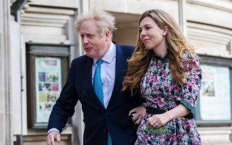 epa09180229 Britain's Prime Minster Boris Johnson (L) and his partner Carrie Symonds arrive at a polling station to cast their votes for the local elections in London, Britain, 06 May 2021. Britons go to the polls on 06 May 2021 to vote in local and mayoral elections.  EPA/VICKIE FLORES
