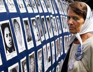 BUENOS AIRES, ARGENTINA:  Tati Almeida observes a flag with pictures of disappeared victims in Buenos Aires, Argentina 04 December 2002.  Tati Almeida, integrante de la organizaci=n Madres de Plaza de Mayo, (Linea Fundadora), observa una gran bandera con fotos de desaparecidos durante la pasada dictadura militar (1976-1983) colgada frente a la Casa de Gobierno en Buenos Aires, Argentina, el 04 de diciembre de 2002. Convocado por Madres de Plaza de Mayo-Linea fundadora y varios organismos humanitarios, se inici= la XXII Marcha anual de la Resistencia de 24 horas en la Plaza de Mayo, en homenaje a los desaparecidos y a las vfctimas por la represi=n policial en democracia.    AFP PHOTO/Ali BURAFI (Photo credit should read ALI BURAFI/AFP via Getty Images)