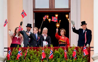 King Harald V of Norway (R), Queen Sonja of Norway (2nd R), Crown Prince Haakon of Norway (2nd L), Crown Princess Mette-Marit of Norway (C), Princess Ingrid Alexandra (L) and Prince Sverre Magnus (3rd L) wave Norwegian flags during celebrations of the Constitution Day on May 17, 2020 in Oslo. - The holiday is celebrated in a new and different way this year because of the novel coronavirus. (Photo by Lise Åserud / NTB Scanpix / AFP) / Norway OUT (Photo by LISE ASERUD/NTB Scanpix/AFP via Getty Images)