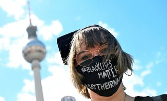 "A protester poses with a slogan ""black livres matter"" at Alexanderplatz square during a demonstration in solidarity with protests raging across the US over the death of George Floyd on June 6, 2020 in Berlin. - The death during the arrest of George Floyd, an unarmed black man in the US state of Minnesota, has brought tens of thousands out onto the streets during a pandemic that is ebbing in Asia and Europe, but spreading in other parts of the world. (Photo by Tobias SCHWARZ / AFP) (Photo by TOBIAS SCHWARZ/AFP via Getty Images)"