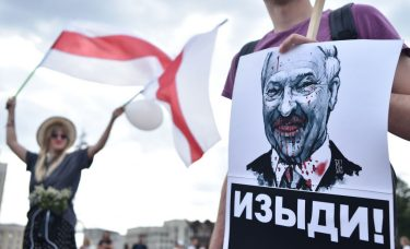 """A man holds a picture of the Belarus President Alexander Lukashenko reading """"Go away!"""" during a protest rally against police violence during recent rallies of opposition supporters, who accuse strongman Alexander Lukashenko of falsifying the polls in the presidential election, in central Minsk on August 14, 2020. - Crowds of workers walked off the job on August 14, 2020, at several factories in Belarus's capital Minsk in support of the opposition calling for leader Alexander Lukashenko to step down. Hundreds of workers marched from the Minsk Automobile Plant (MAZ) and the Minsk Tractor Works (MTZ) after the opposition called for strikes against Lukashenko's disputed claim to have won re-election. (Photo by Sergei GAPON / AFP) (Photo by SERGEI GAPON/AFP via Getty Images)"""