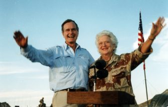 politician US President George HW Bush and First Lady Barbara Bush wave from a lectern, Saudi Arabia, November 22, 1990. The visit, occurring during Operation Desert Shield, was part of a Thanksgiving tour. (Photo by Chief Warrant Officer 2 Ed Bailey/PhotoQuest/Getty Images)