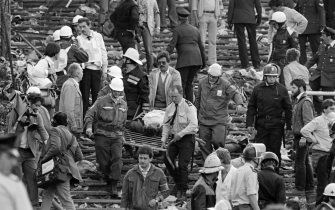 Rescuers evacuate a victim on May 29, 1985 at Heysel football stadium in Brussels after 39 people lost their lives in violent incidents, one hour before the European Champion Clubs final between Britain's Liverpool and Italy's Juventus of Turin. The tragedy occured when a wall collapsed in the stadium under the pressure of people and crushed Juventus fans as they tried to escape Liverpool supporters. 39 fans died and more than 600 were injured. (Photo by DOMINIQUE FAGET / AFP) (Photo by DOMINIQUE FAGET/AFP via Getty Images)