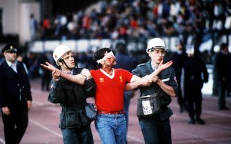 AN INJURED LIVERPOOL SOCCER FAN IS LED AWAY BY MEDICAL STAFF PRIOR TO THE 1985 EUROPEAN CUP FINAL AT THE HEYSEL STADIUM, BELGIUM. ITALIAN FANS WERE KILLED AFTER A WALL COLLAPSED BEFORE JUVENTUS BEAT LIVERPOOL 1-0 IN THE GAME.