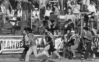 Italian fans run on May 29, 1985 in Heysel stadium in Brussels, as violence has broken out one hour before the European Champion Clubs final between Britain's Liverpool and Italy's Juventus of Turin, killing 39 fans and injuring more than 600. The tragedy occured when a wall collapsed in the stadium under the pressure of people and crushed Juventus fans as they tried to escape Liverpool supporters.        (Photo credit should read DOMINIQUE FAGET/AFP via Getty Images)