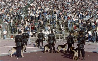 Belgium policemen with dogs face Italian fans, on May 29, 1985 in Heysel stadium in Brussels, as violence has broken out one hour before the European Champion Clubs final between Britain's Liverpool and Italy's Juventus of Turin, killing 39 fans and injuring more than 600. The tragedy occured when a wall collapsed in the stadium under the pressure of people and crushed Juventus fans as they tried to escape Liverpool supporters.        (Photo credit should read DOMINIQUE FAGET/AFP via Getty Images)
