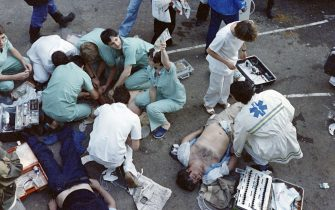 Rescuers attend victims on May 29, 1985 after 39 people lost their lives and more than 600 others were injured in violent incidents inside the stadium, an hour before the kick off of the European Champion Clubs final between Britain's Liverpool and Italy's Juventus of Turin at Heysel stadium. The tragedy occured when a wall collapsed in the stadium under the pressure of people and crushed Juventus fans as they tried to escape Liverpool supporters. (Photo by DOMINIQUE FAGET / AFP) (Photo by DOMINIQUE FAGET/AFP via Getty Images)
