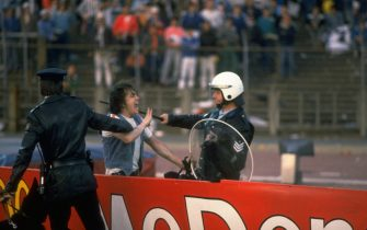 29 May 1985:  A supporter is restrained and hit with a baton by police during the crowd riots at the European Cup Final between Liverpool and Juventus at the Heysel Stadium in Brussels, Belgium. Juventus won the match 1-0. \ Mandatory Credit: David  Cannon/Allsport