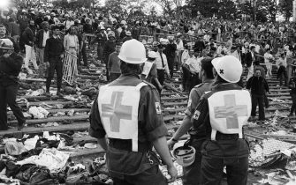 Rescuers attend 29 May 1985 victims at the scene of riots in Heysel football stadium in Brussels after thirty-nine Juventus football fans died during rioting at the European Cup Final in Brussels. The tragedy occured when a wall collapsed in the stadium and crushed Juventus fans as they tried to escape Liverpool supporters. The two sets of supporters had spent the day drinking in the Belgian city and had arrived at the Heysel stadium waving flags and chanting. Shortly before kick off the atmosphere turned violent and Liverpool supporters stampeded through a thin line of police towards the rival fans. As the Juventus fans retreated a wall collapsed under the pressure and fans were crushed and trampled to death in the panic. AFP PHOTO DOMINIQUE FAGET        (Photo credit should read DOMINIQUE FAGET/AFP via Getty Images)