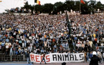"""Belgium policemen face Italian fans holding a banner where is written """"Reds animals"""", on May 29, 1985 in Heysel stadium in Brussels, as violence has broken out one hour before the European Champion Clubs final between Britain's Liverpool and Italy's Juventus of Turin, killing 39 fans and injuring more than 600. The tragedy occured when a wall collapsed in the stadium under the pressure of people and crushed Juventus fans as they tried to escape Liverpool supporters.        (Photo credit should read DOMINIQUE FAGET/AFP via Getty Images)"""