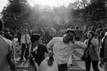 Supporters flee 29 May 1985 the scene of riots in Heysel football stadium in Brussels after thirty-nine Juventus football fans died during rioting at the European Cup Final in Brussels. Shortly before kick off the atmosphere turned violent and Liverpool supporters stampeded through a thin line of police towards the rival fans. As the Juventus fans retreated a wall collapsed under the pressure and fans were crushed and trampled to death in the panic. AFP PHOTO DOMINIQUE FAGET / AFP PHOTO / DOMINIQUE FAGET        (Photo credit should read DOMINIQUE FAGET/AFP via Getty Images)